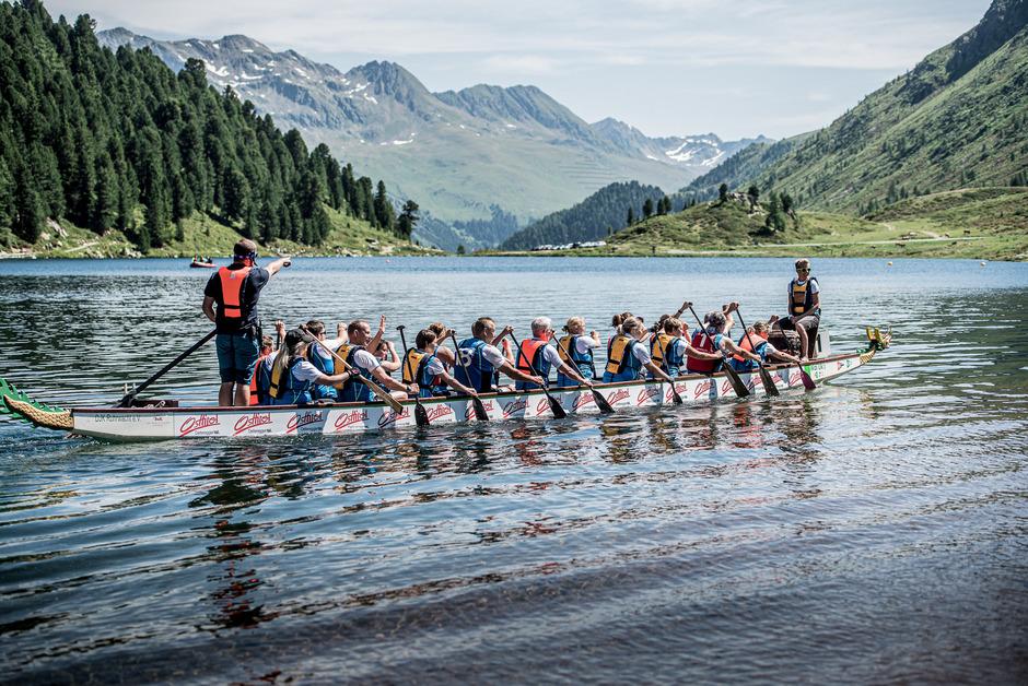 Zwischen 16 und 20 Teammitglieder rudern bei den Drachenbootrennen am Obersee in einem Boot.