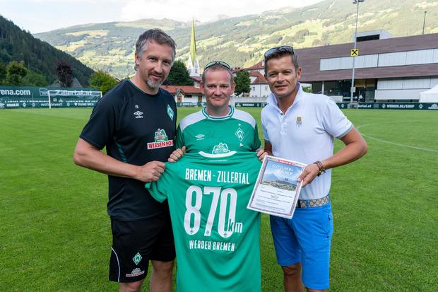 Ein Werder-Trikot-Unikat und einen Hotel-Gutschein überreichten Frank Baumann, GF Fußball Werder Bremen (l.), und Ferdinand Lechner jun., Obmann TVB Zell-Gerlos (r.), an Maik Kuntze.