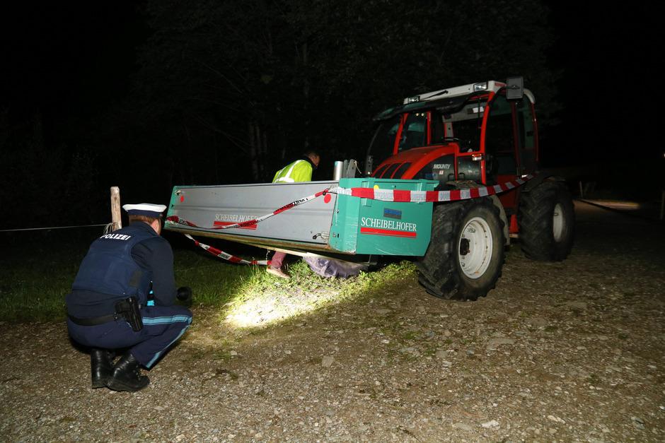 Polizisten untersuchen einen Traktor, nachdem zwei Kinder von dem Fahrzeug überrollt  wurden und dabei ums Leben gekommen sind.