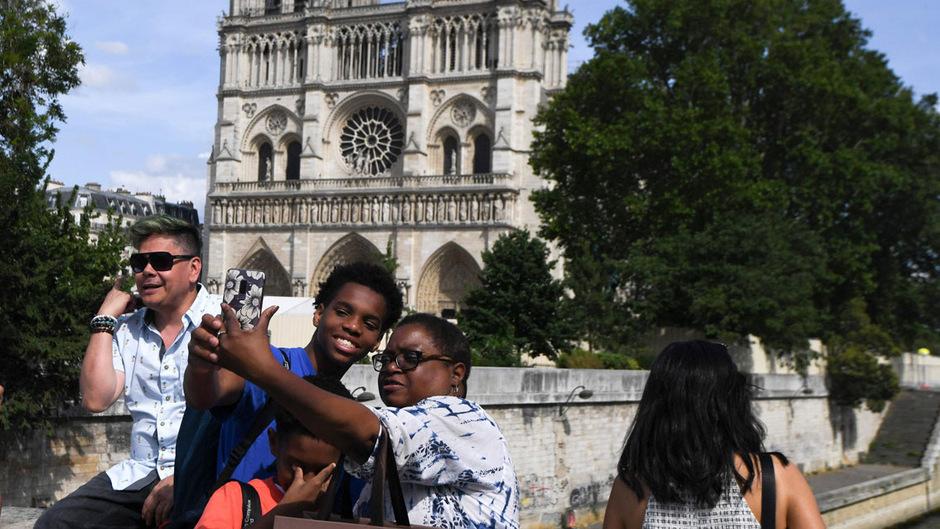 Touristen machen Fotos vor dem zerstörten Wahrzeichen.