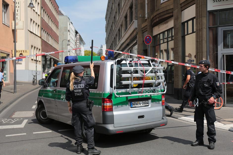 Polizisten sperren in der Kölner Innenstadt eine Straße mit einem Absperrband ab.