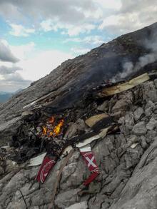 Fotos zeigten Trümmer des Flugzeuges in einer Felswand.