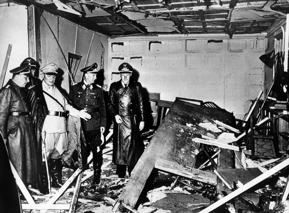 """Reichsmarschall Hermann Göring (helle Uniform) und der Chef der """"Kanzlei des Führers"""", Martin Bormann (l.), begutachten die Zerstörung im Raum der Karten-Baracke in Rastenburg, wo Stauffenberg am 20. Juli 1944 eine Sprengladung zündete."""