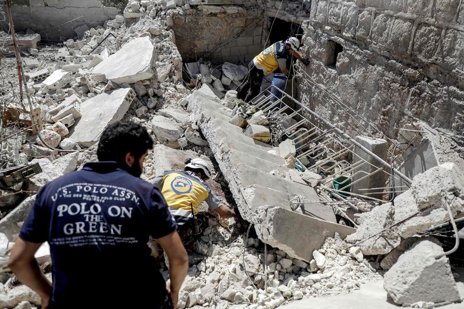 Syrische Weißhelme suchen in den Trümmern eines Gebäudes in Kafar Roma nach Überlebenden und Opfern.