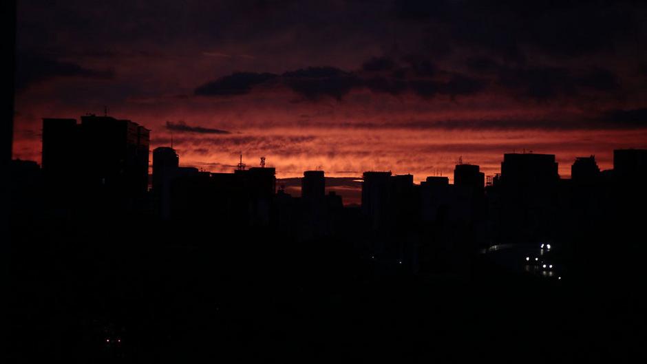 Die Sonne geht hinter dunklen Häusern in Caracas unter.