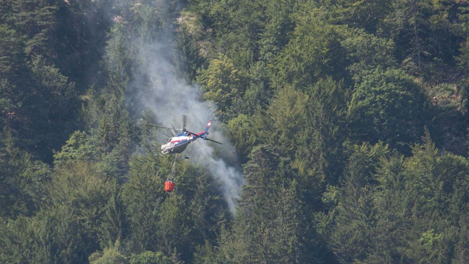 Im Bereich Hechenberg oberhalb von Innsbruck brach ein Waldbrand aus - der Polizeihubschrauber ist im Löscheinsatz.