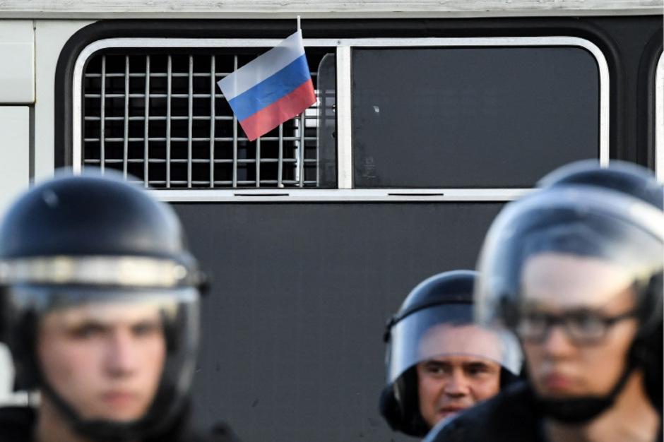 Ein inhaftierter Demonstrant zeigt die russische Flagge.