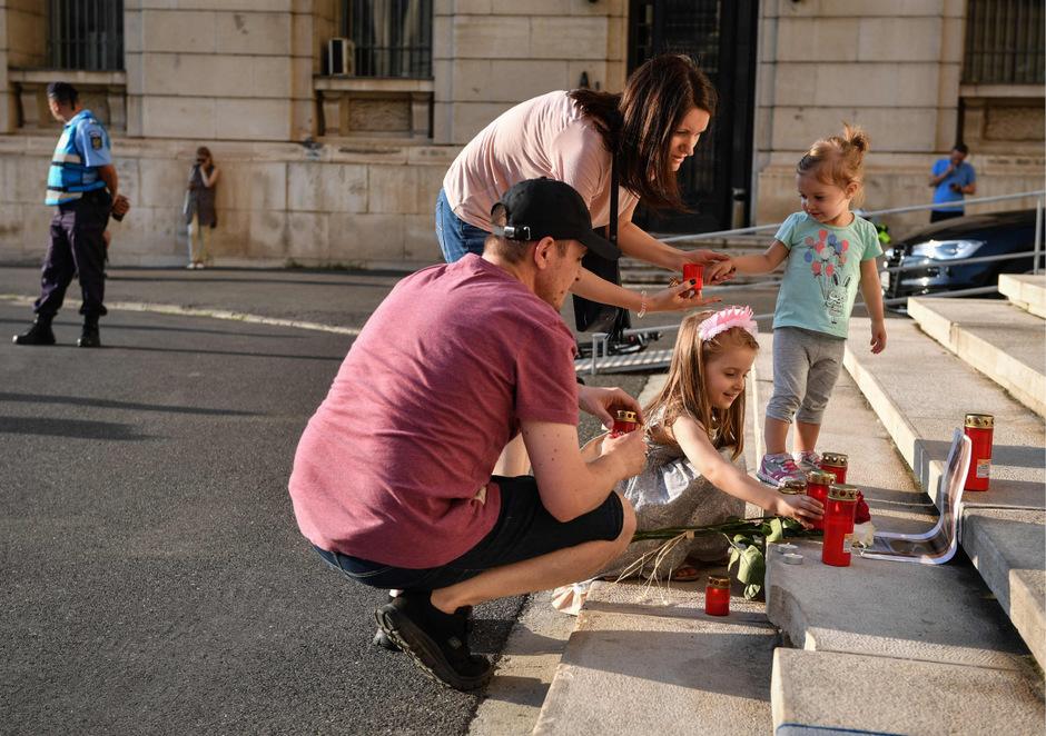 Eine Familie zündet Kerzen vor dem innenministerium in Bukarest an.