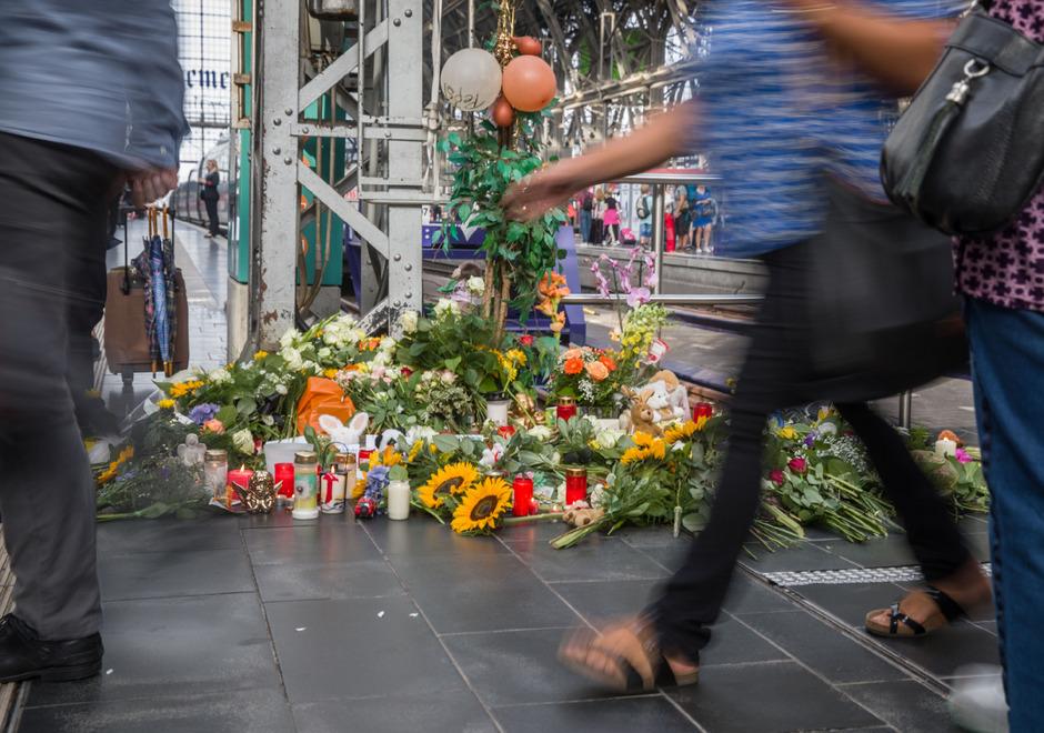 Reisende und Pendler gehen am Morgen am Bahnsteig 7 im Frankfurter Hauptbahnhof an den abgelegten Blumen, Kerzen und Plüschtieren vorbei.