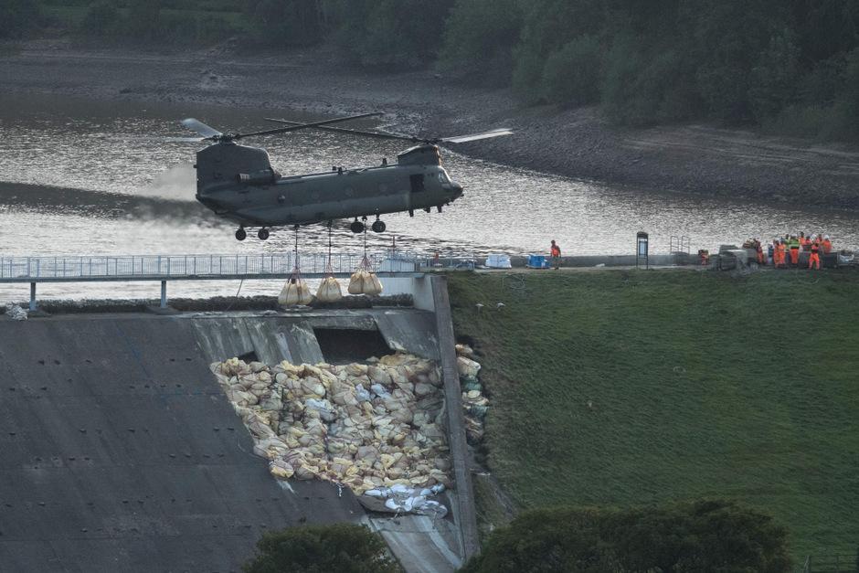 Ein Hubschrauber bringt Sandsäcke an die Staumauer.