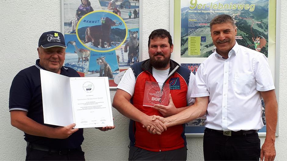 Wolfgang Moosbrugger (Geschäftsführer der Tannheimer Bergbahnen, r.) übergibt das Dekret aus Wien an die Belegschaftsvertreter Peter Specht (Betriebsleiter, l.) und Bertram Kofler (Betriebsratsobmann).
