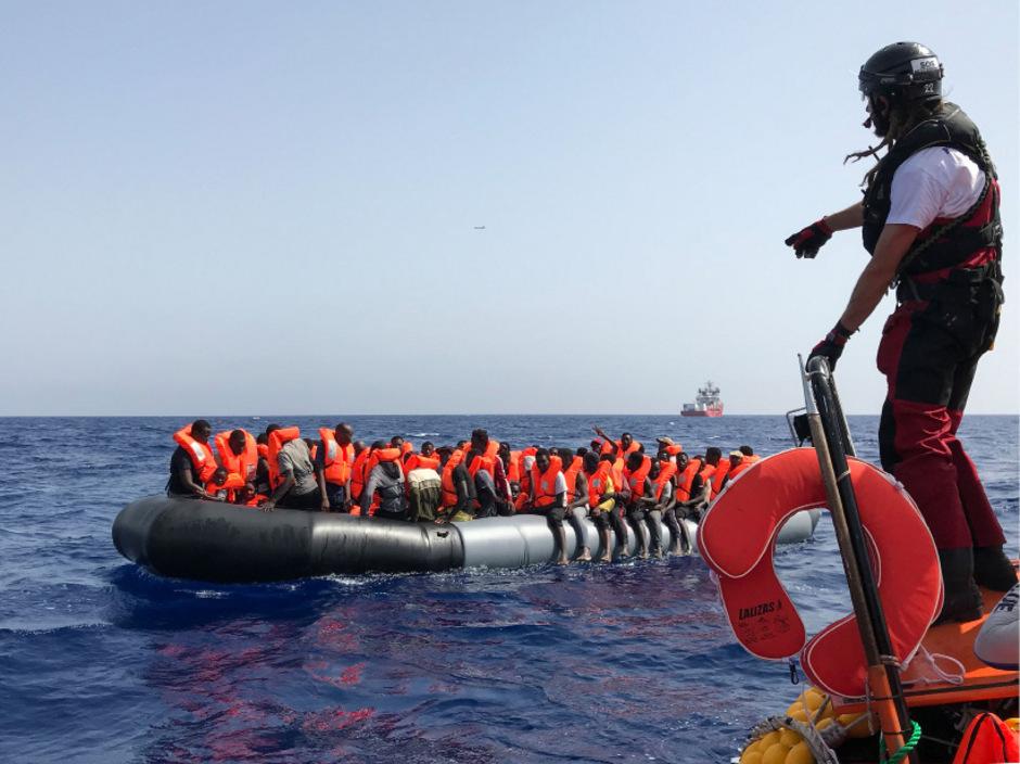 """Ein Seenotretter der """"Ocean Viking"""" gibt Migranten in einem Schlauchboot Anweisungen."""