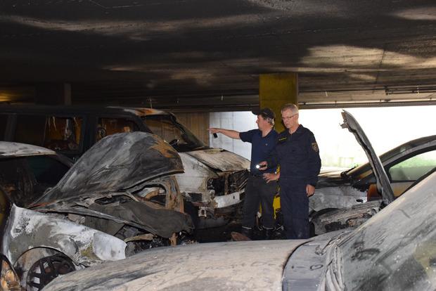 Die Brandermittler Josef Rohregger (l.) und Roland Egger suchen inmitten der ausgebrannten Wracks nach Spuren zur Brandursache.