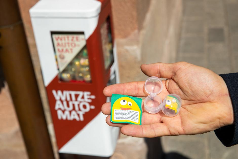 In dem umgebauten Kaugummiautomaten befinden sich Kapseln, die mit kleinen Zetteln mit je einem Witz bestückt sind.