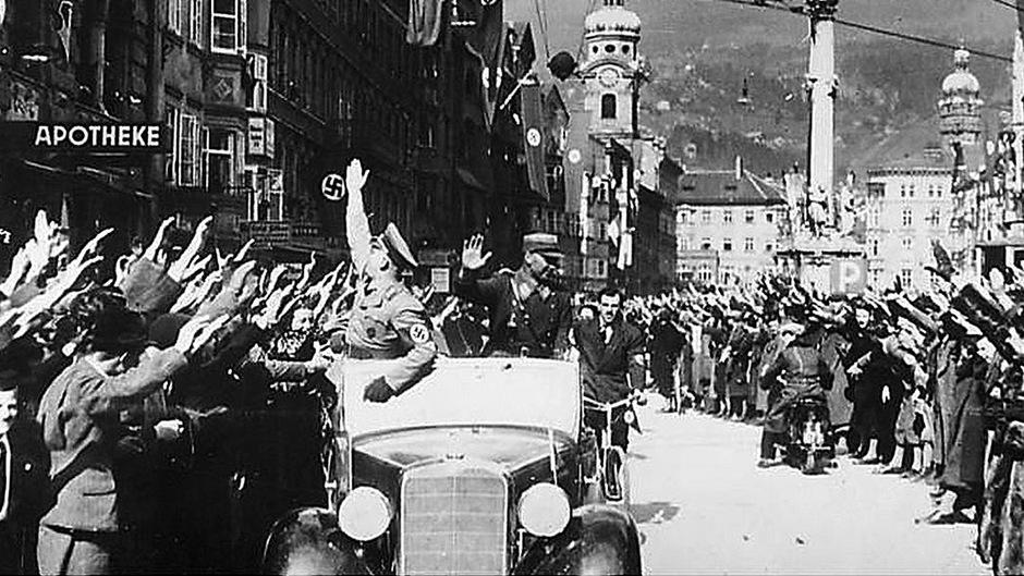 Dieses Bild wurde am 12. März 1938 aufgenommen. Es zeigt Menschen in der Maria-Theresien-Straße in Innsbruck, die deutsche Wehrmachtssoldaten jubelnd empfangen.