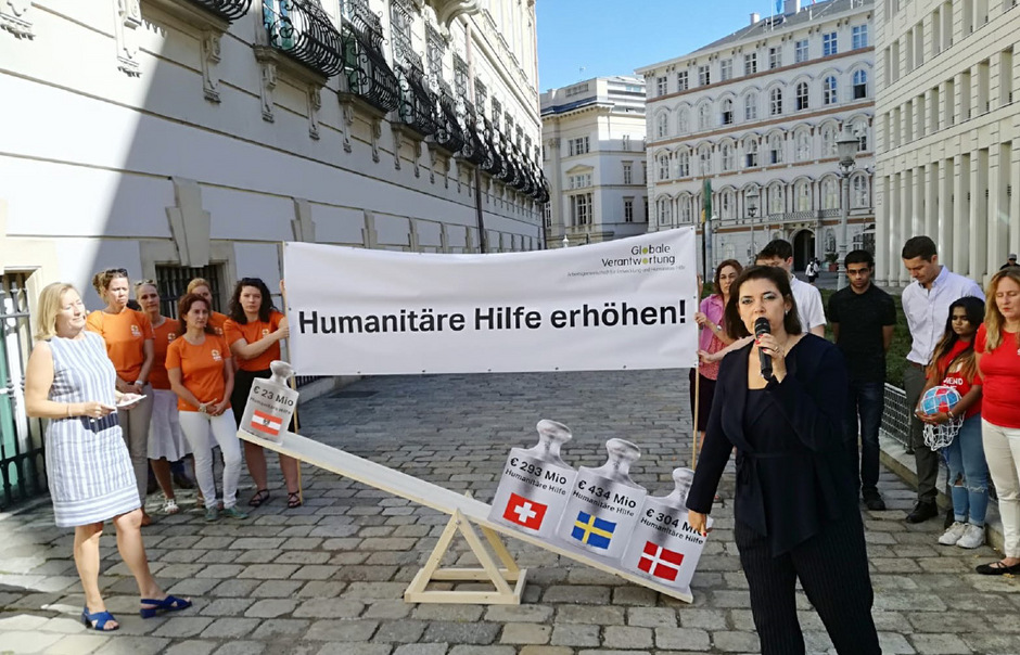 """Veranschaulicht wurden die Länderunterschiede bei der Protestaktion nahe des Wiener Ballhausplatzes mit einer Waage, die angesichts des """"Leichtgewichts humanitäre Hilfe"""" klar auf eine Seite kippte."""
