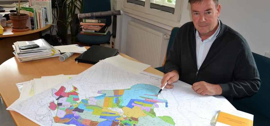 Hubert Mühlmann, Leiter der Agrar Lienz, mit einem Grundstücksplan von Abfaltern, jedem Grundbesitzer ist eine Farbe zugeordnet. Einige Flächen sind fast zur Gänze von fremdem Grund umschlossen.