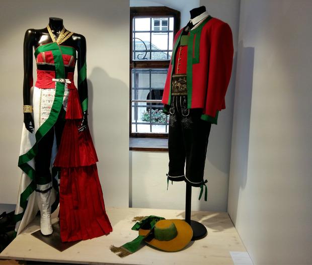 Pustertaler Tracht einmal anders: Anna Oberdorfer interpretiert Farben und Aussehen neu und gestaltet ein schulterfreies Abendkleid, das mit weißen Stiefeln getragen wird.