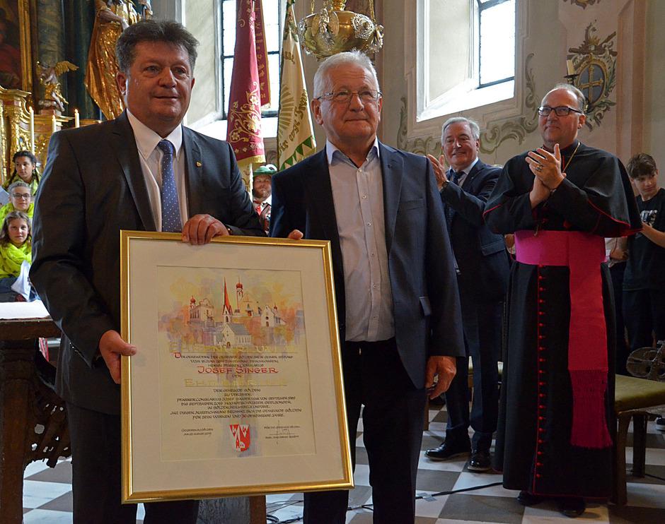 BM Ernst Schöpf überreicht die Ehrenring-Urkunde an Pfarrer Josef Singer; Dekan Stefan Hauser und Bischof Hermann Glettler applaudieren.