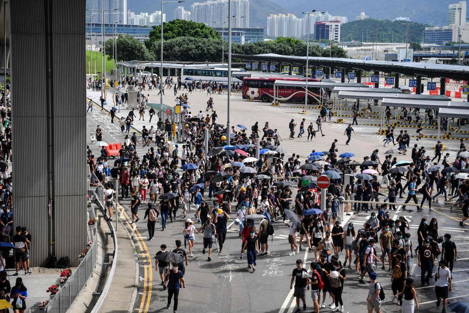 Aktivisten, die sich mit Regenschirmen gegen Überwachungskameras abschirmten, errichteten Barrikaden am Busbahnhof des Flughafens und versuchten, die größte Zufahrtsstraße zum Terminal zu blockieren.