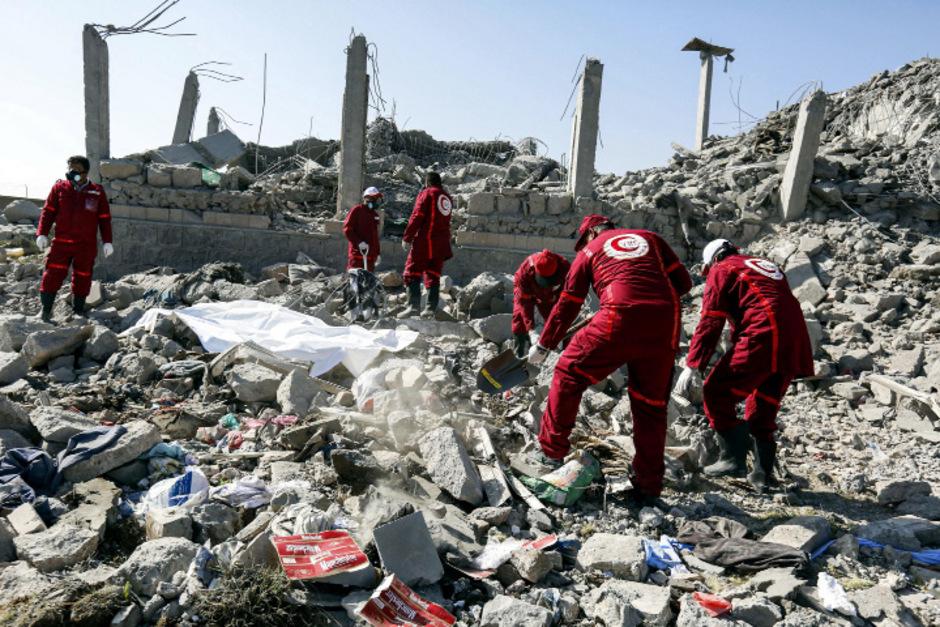 Helfer suchen nach Überlebenden unter den Trümmern des Gefängnisses.
