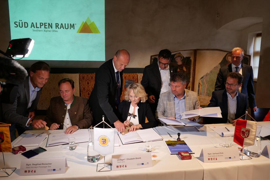 Die Bürgermeister Siegfried Ronacher (Hermagor), Elisabeth Blanik, Gerhard Pirih (Spittal an der Drau) und Roland Griesmair (Bruneck) haben das Vertragswerk auf Schloss Bruck unterzeichnet (sitzend, v.l).