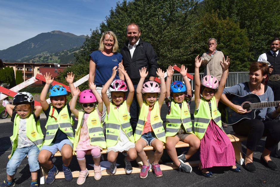 Kindergartenleiterin Susanne Hotter und LHStv. Josef Geisler freuen sich mit den Kleinen über die Brücke, die ihnen einen gefahrlosen Weg zum Kindergarten ermöglicht.