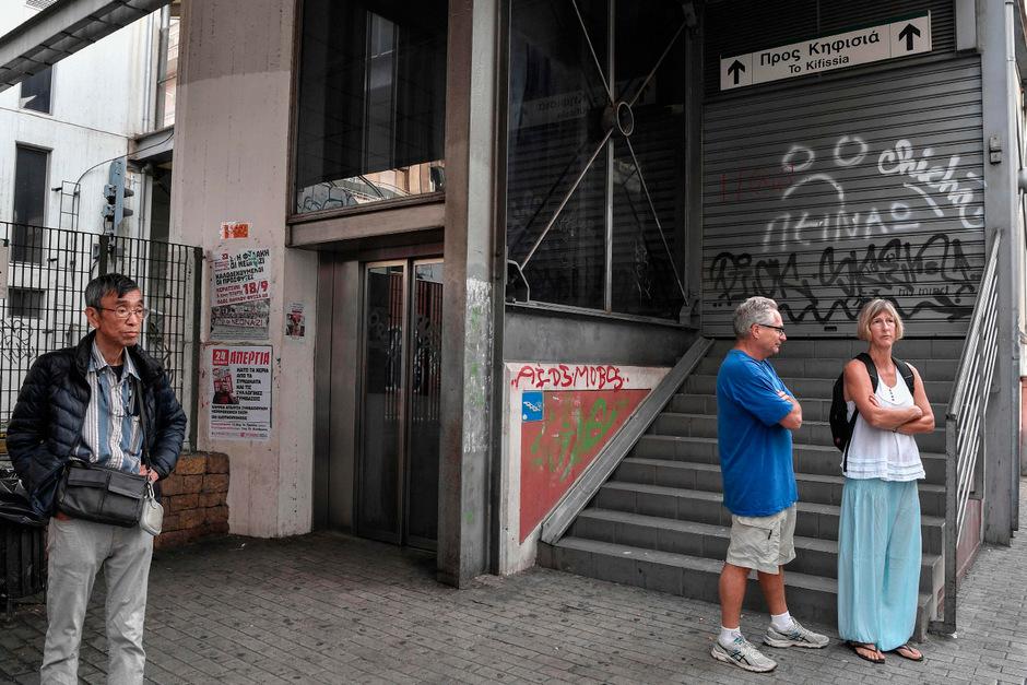Touristen stehen vor dem geschlossenen Eingang zu einer U-Bahn-Station. Wegen des Streiks fahren die Züge nicht.