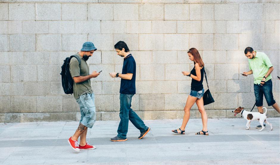 """Wer nur noch auf sein Smartphone starrt und von seiner Umwelt nichts mehr mitbekommt, wird """"Smombie"""" genannt. Das Kofferwort aus den Begriffen """"Smartphone"""" und """"Zombie"""" wurde 2015 zum Jugendwort des Jahres gewählt."""
