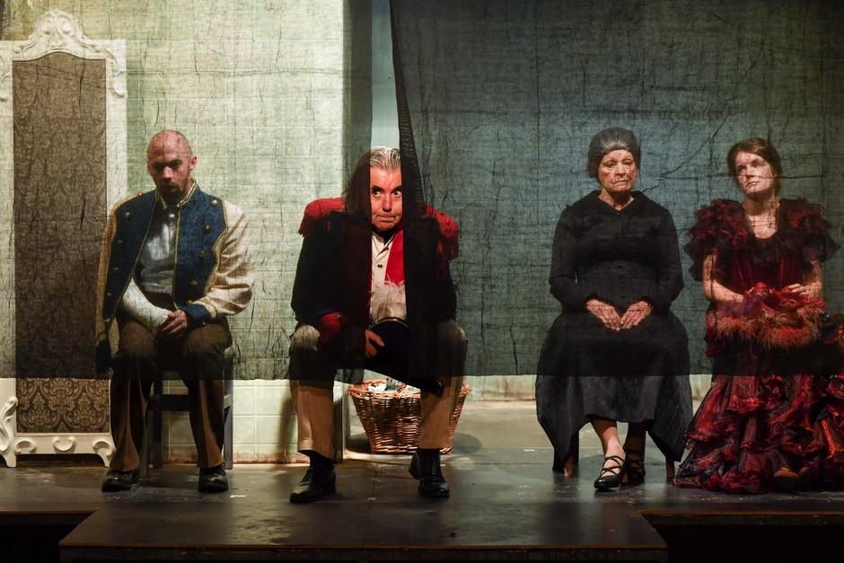 """Ist da jemand? Theaterdespot Bruscon (Klaus Rohrmoser) lugt durch den Bühnenvorhang. Die """"untalentierte Brut"""", (v.l.) Sohn Ferruccio (Edwin Hochmuth), Frau Agathe (Susanne Schartner) und Tochter Sarah (Wiltrud Stieger), macht böse Miene zum bösen Spiel."""