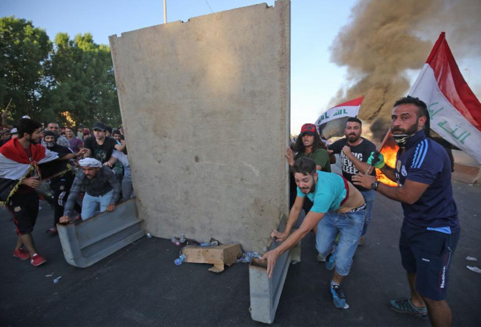 Demonstranten in Bagdad gehen in Deckung.