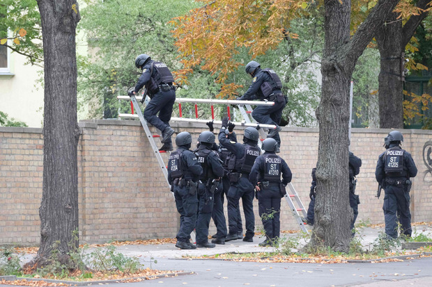 Polizisten klettern über die Mauer des Jüdischen Friedhofs in Halle.