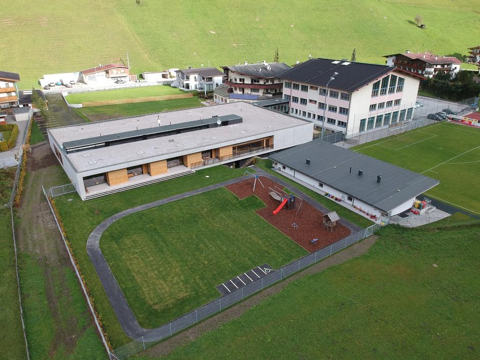 Der Kindergarten (Flachbau) ist an das Schulgebäude rechts daneben angegliedert.