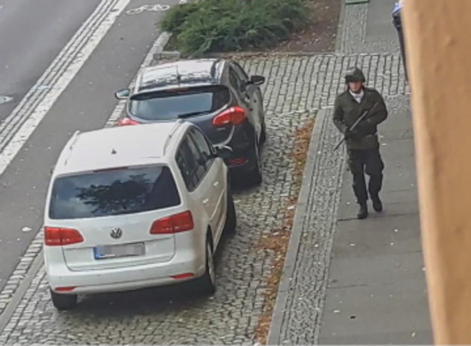 Auf diesem Video-Screenshot ist ein schwerbewaffneter Mann in schwarzer Kampfmontur und Stahlhelm zu sehen. Der Mann in dem mutmaßlichen Bekennervideo trägt die selbe Kleidung.