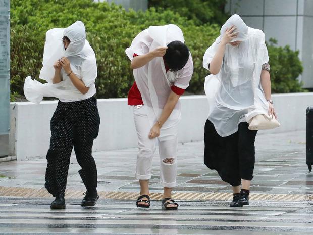 Menschen versuchen in Nagoya gegen den starken Wind anzukommen.