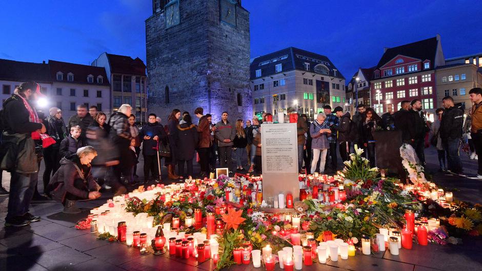 Trauernde versammeln sich um ein Denkmal aus Blumen und Kerzen.