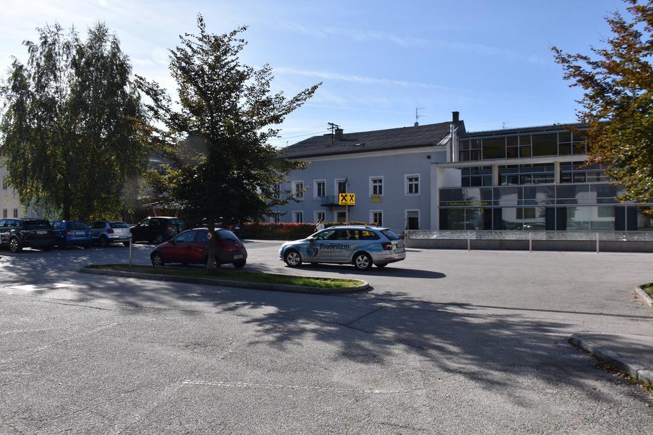 Der Parkplatz zwischen der Bank und dem Postpark samt Kindergarten soll ab nächstem Jahr zum Raiffeisen Quartier umgebaut werden.