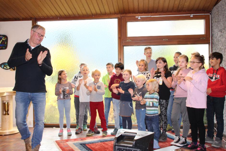 Kinderliedermacher Reinhard Horn (links) probt mit den jungen Leuten für den Auftritt.