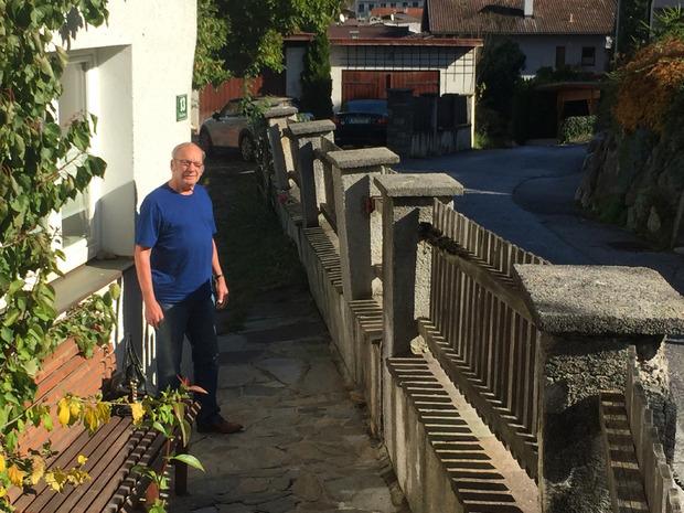 Heinz Schnaiter vor seiner Gartenmauer. Dort, wo die Gemeindestraße bis zum Sockelende aufgeschüttet wurde, neigt sie sich talwärts.
