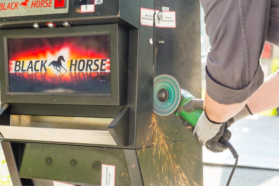 Ein Beamter beim Aufschneiden eines Spielautomaten: Illegales Glücksspiel wird auch immer wieder in Wettlokalen angeboten.