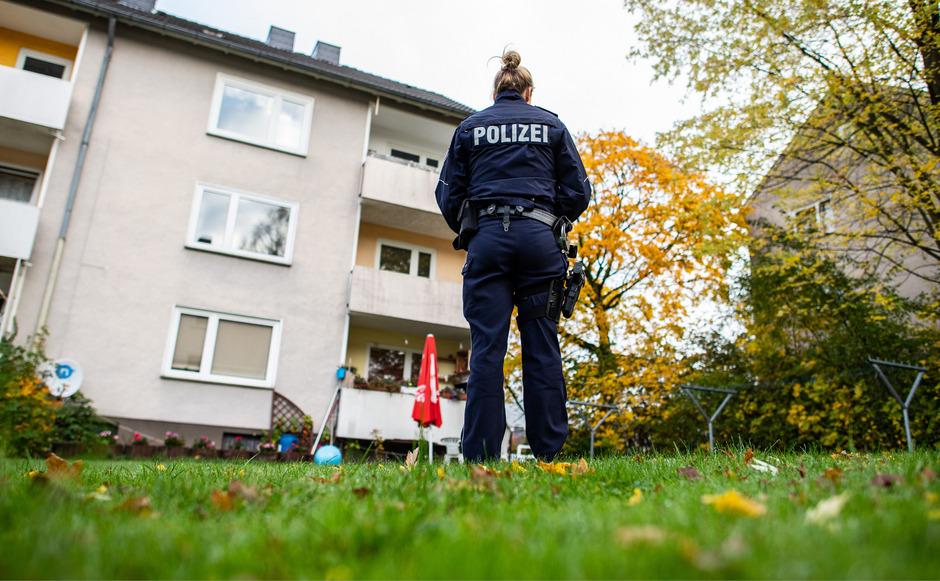 Eine Polizistin steht im Garten des Mehrfamilienhauses in Detmold, in dem eine 15-Jährige ihren dreijährigen Halbbrudermit einem Messer getötet haben soll.