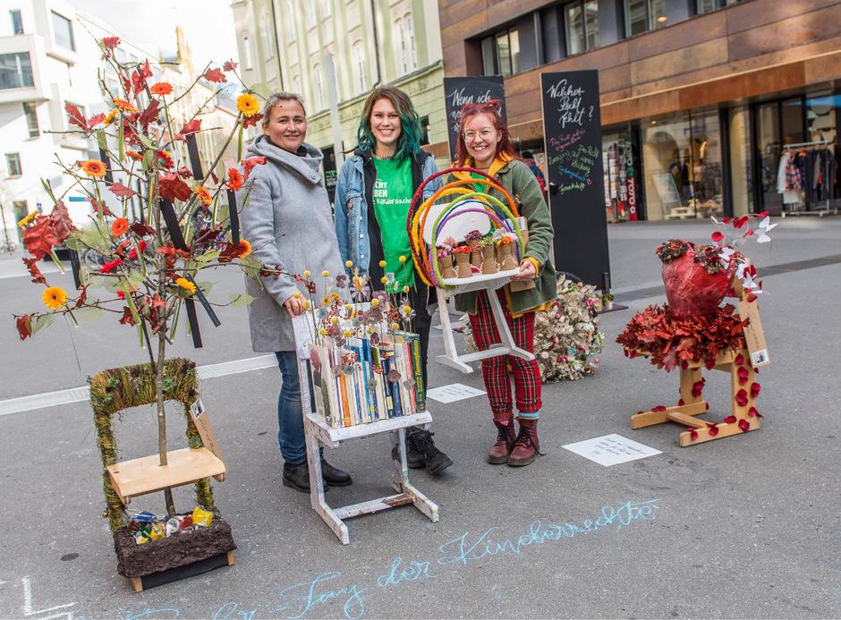 """Eva Baumann (Lehrerin der Tiroler FBS für Garten, Raum und Mode) und Enola und Theresa (v.l.), zwei der Schülerinnen, mit ihren Abschlussarbeiten, den """"Kinderrechte-Stühlen""""."""