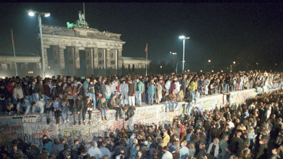 Die Bilder, wie am Brandenburger Tor oben auf der Mauer getanzt wird und die DDR-Grenzschützer zusehen, gehen um den Globus.