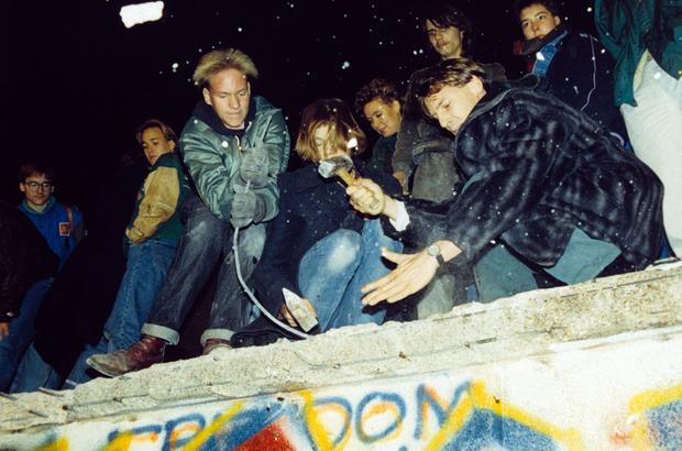 West-Berliner versuchen am 10. November mit Hämmern und Kreuzhacken die Berliner Mauer einzureißen.