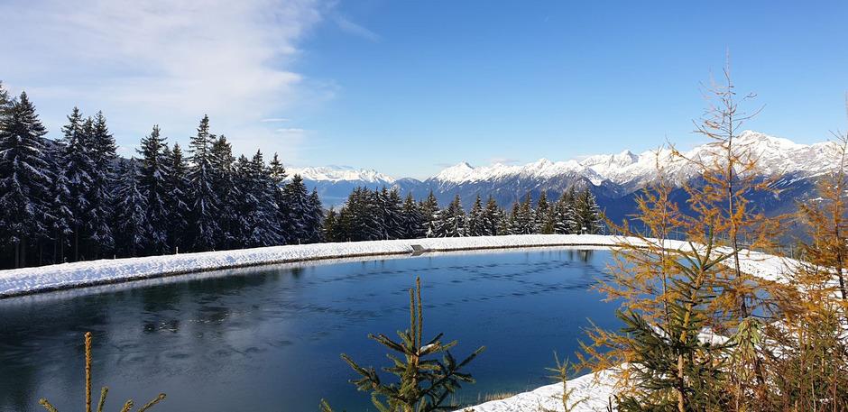 Speichersee in Hütteg am Weerberg von Schnee umrahmt.