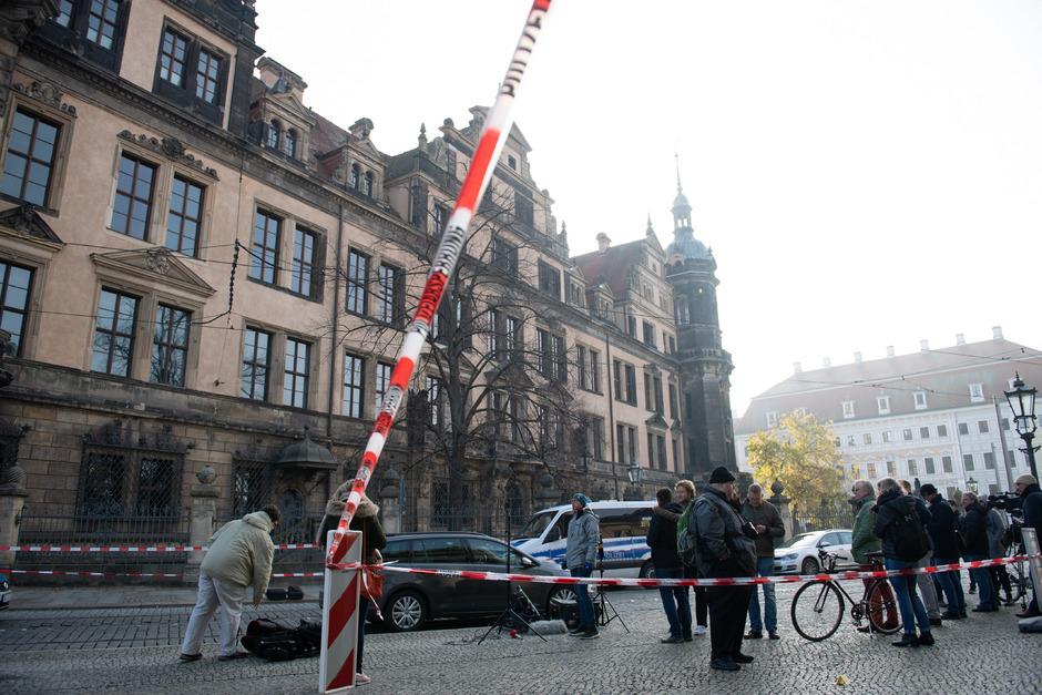 Journalisten und Passanten stehen vor dem Residenzschloss mit dem Grünen Gewölbe hinter einem Absperrband.