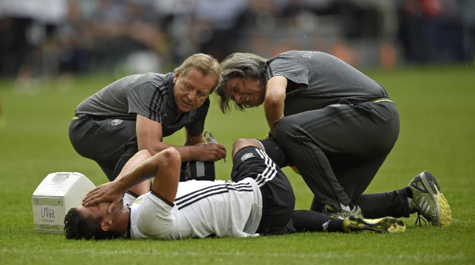 """Wenn Nationalspieler wie Sami Khedira am Boden liegen, sind Hände gefragt, die sehen können: solche wie jene von Hans-Wilhelm Müller-Wohlfahrt (r.). """"Viele haben verlernt, Verletzungen zu ertasten."""""""