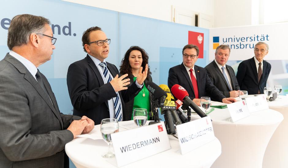 Martin Widschwendter (2.v.l.) präsentiert Christian Wiedermann (Tirol Kliniken/l.), LH Günther Platter, LHStv. Ingrid Felipe, Gesundheits-LR Bernhard Tilg und Tilmann Märk (Rektor der Uni Innsbruck) sein Konzept.